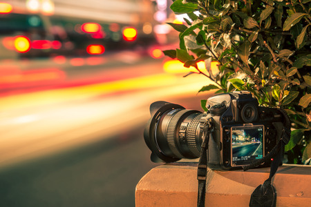 Travel Photography Concept. Professional Digital Camera and Traffic Blurs. Night Long Exposure Photography.