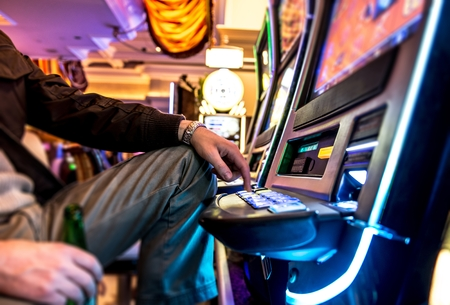 gambler: Gambler and Slot Machine. Men with Beer Playing Slots in Vegas Casino.