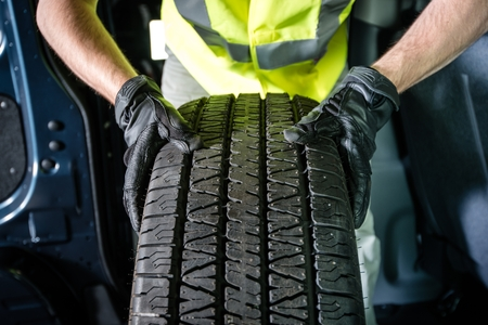 installation: Car Tire Replacement. Tire Service. Men with Brand New Tire is Ready For Installation.