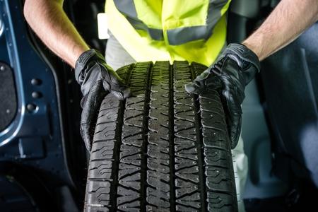 neumaticos: Sustituci�n de neum�ticos de coche. Tire Service. Los hombres con nueva marca de neum�ticos est� listo para la instalaci�n.
