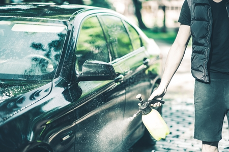car body: Spraying Car Body Wax. Car Waxing Closeup. Stock Photo