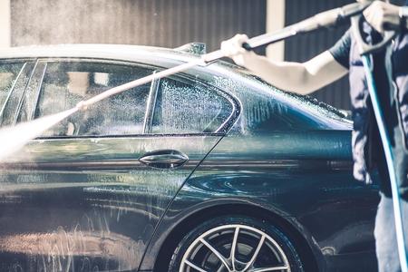 autolavado: Los hombres se lava el coche utilizando alta presión de agua.