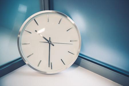 timeless: Modern Wall Clock in Between Frozen Glass Walls. Elegant Wall Clock. Stock Photo