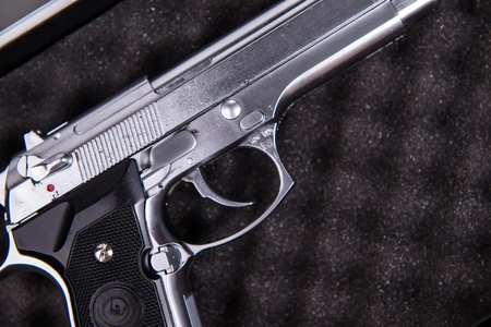 Silver Dirty Handgun on Black Foam Closeup