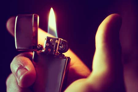 fireplace lighter: Lighting Up the Lighter Closeup Photo. Cool Metallic Lighter in a Hand. Stock Photo
