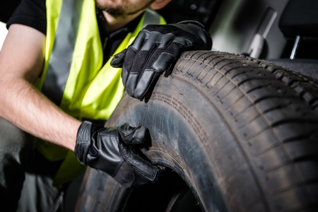 Car Service Worker Replacing Car Tire.