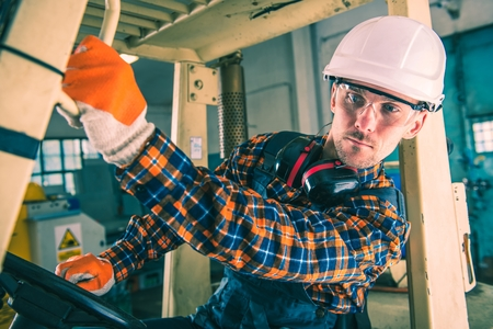 machinery: Forklift Driving Operator. Forklift Works. Caucasian Worker Inside the Machine. Stock Photo