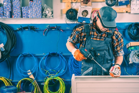 Worker and His Workstation. Worker with Screwing Gun. Small Business. Stock Photo