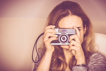 photo pictures: Vintage Camera Photography. Young Woman in Her 20s Taking Pictures Using Aged Vintage Photo Camera.