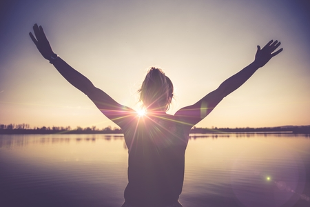 Life Happiness and Joy. Caucasian Woman Holding Arms Up To the Sky and Breathing Deeply Enjoying Her Life. Lake Shore.