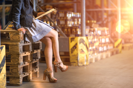 Business woman sitting on a pallets in a warehouse checking reports.