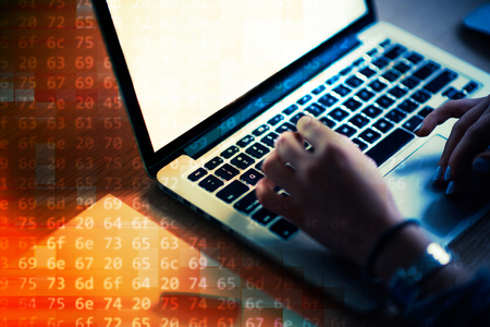 Woman programmer writing a code. Female programmer hands on the keyboard. Orange background. Stock Photo