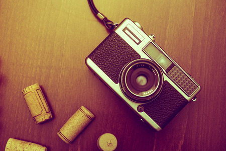 Retro camera and wine corks on wood table background, vintage color tone