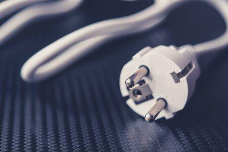 European power cable on carbon background closeup photo. White color.