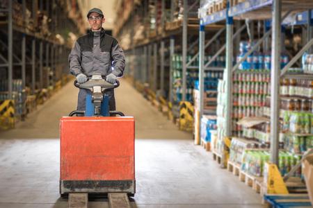 skids: Caucasian Worker in uniform with pallet jack
