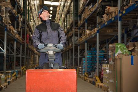 skids: Caucasian Worker in uniform with pallet jack looking for package
