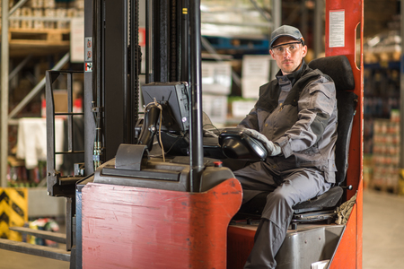 Caucasian fork lift truck driver waiting for delivery.