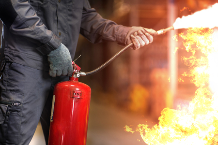 Man using fire extinguisher fighting fire closeup photo.