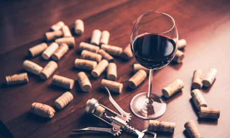 Red wine glass, corks and corkscrew on wooden table.