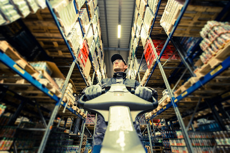 skids: Caucasian Worker in uniform with pallet jack looking for package. Closeup photo. Stock Photo