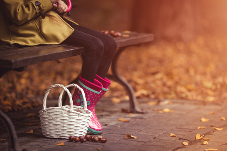 Young girl holding umbrella and sitting at the bench. Autumn theme. Basket on the ground.