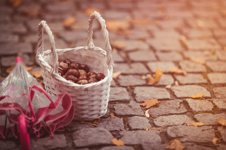 Chestnuts in the basket and umbrella. Autumn theme. Stock Photo