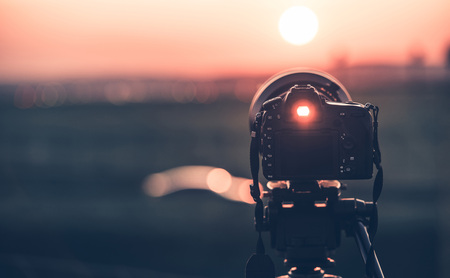 Sunset photography. Camera on tripod shooting colorful sunset. Light passing throught viewfinder.