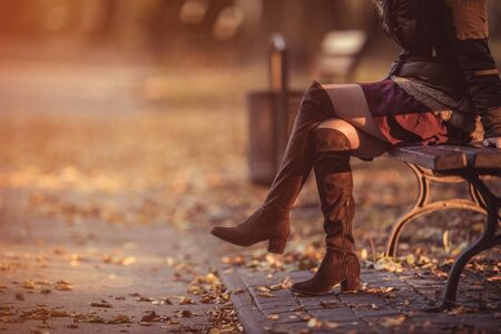 Woman legs at sunset at the park. Autumn theme. Stock Photo