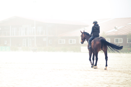 Women riding horse in fog near barn.
