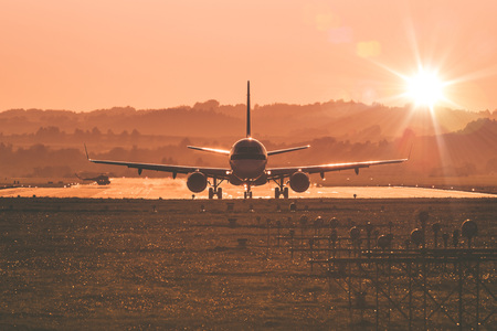 Passengers airplane landing to airport runway in beautiful sunset light.