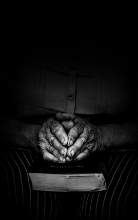 turning table: Elderly woman holds bible and prays black and white