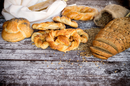 fresh bakery: bread and pretzels topped by sesame seeds over wooden table Stock Photo