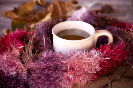 Cup of hot tea dressed in knitted warm winter scarf on brown wooden tabletop photo