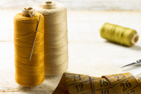 An old style image of cotton reels and other sewing items on a wooden table photo