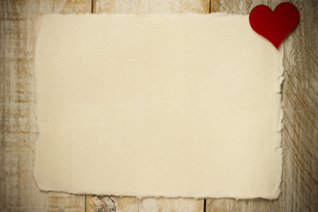 annoucement: red heart over old paper and wooden background Stock Photo