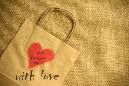 Valentines gift bag with red heart Valentines day background photo
