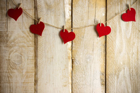 Red hearts hanging over wooden background
