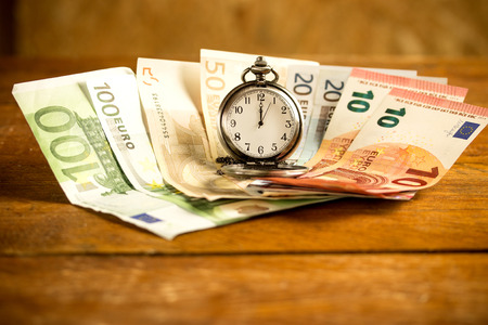 managing money: Euros and a pocket watch on a wooden table