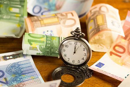 managing money: pocket watch with various banknotes in the background