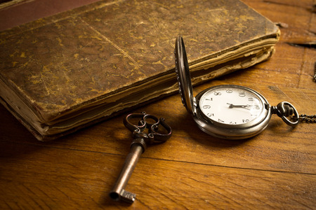 Antique pocket clock showing a few minutes to midnight over ancient books in Low-key. Concept of time,the past or deadline. photo