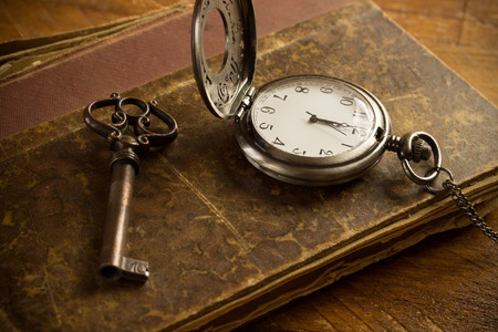 Vintage pocket watch, old book and a brass key on a vintage surface