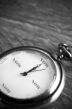 pocket watch on a vintage table showing the time now photo