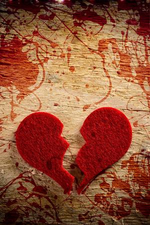 unfaithfulness: broken heart over a wooden background Stock Photo