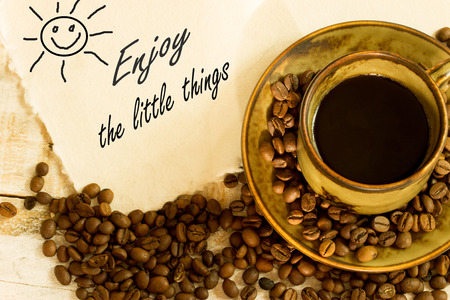cup of black coffee , greeting card with the text enjoy the little things photo