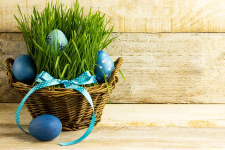 blue easter eggs in a basket, with grass, over wooden background