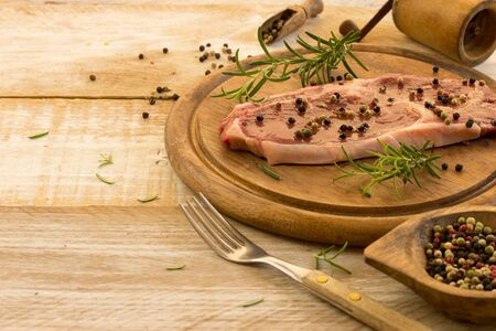 food stuff: raw beef steaks on a wooden table