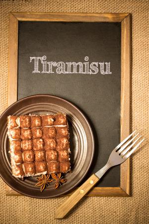 tiramisu cake on a plate, over a chalkboard photo
