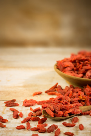 Goji berries on a vintage table in a wooden bowl and spoon Standard-Bild