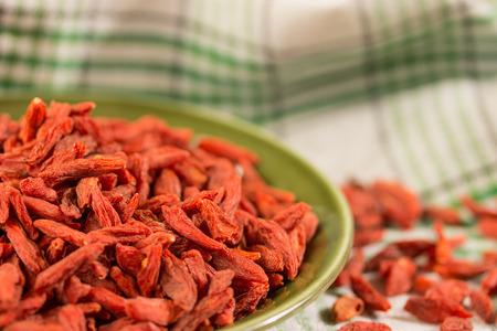 cloesup: goji berries on a green plate cloesup Stock Photo