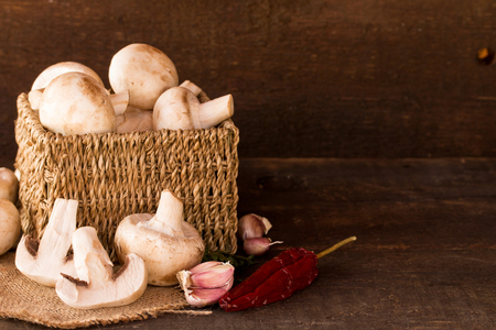 fresh mushroom in a handmade rustic box,over a dark wooden background photo